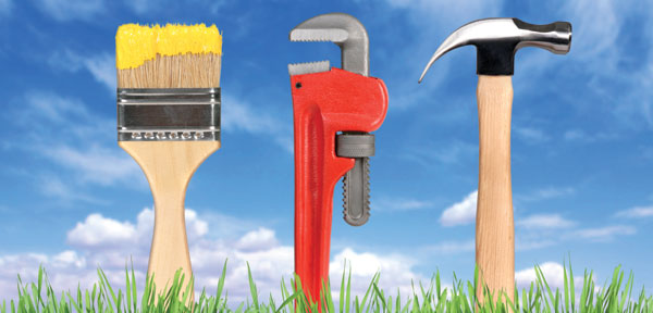 hammer, wrench, paintbrush standing up in grass